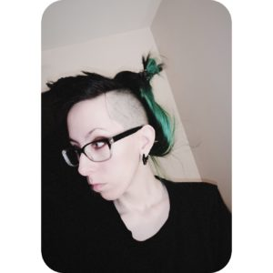 A self-portrait of Nixy who is facing to the side. They have a black and green dyed mohawk hairstyle and are wearing black thick-rimmed glasses and a black teeshirt.